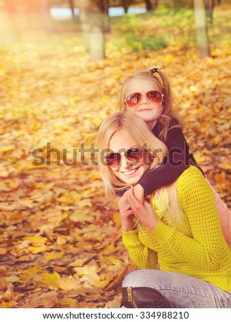 Young mother and little daughter playing fashion dressed in sunglasses in autumn park, girl give a hugs to her mom. - stock photo
