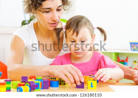 Young mother and little daughter playing with colorful toy blocks - stock photo
