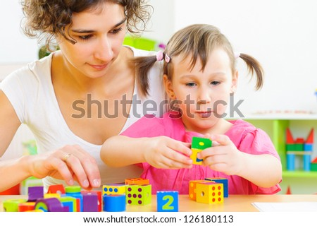 Young mother and little daughter playing with colorful toy blocks