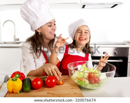 young mother and little daughter preparing salad bowl for lunch wearing apron and cook hat at home kitchen having fun together in healthy vegetable nutrition and education concept - stock photo