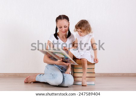 Young mother and little daughter read the books in the room. Happy family. Early development and learning.