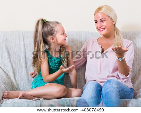 Young mother and little daughter talking and laughing indoors