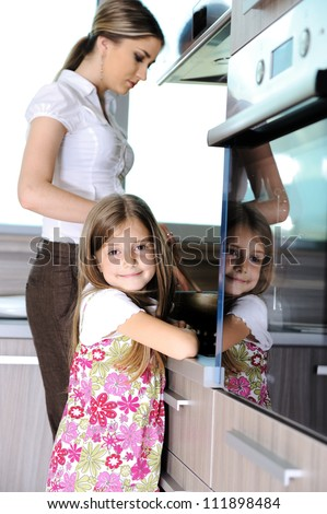 Young mother and little girl daughter in kitchen - stock photo