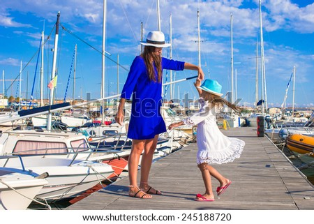 Young mother and little girl in port during summer vacation - stock photo