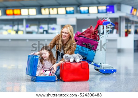 Young mother and little kid girl at the airport. Funny child, daughter and mum, family traveling together, going on vacation via airplane and waiting with suitcases at terminal