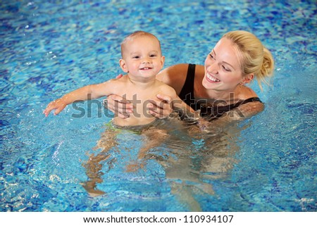 Young mother and little son having fun in a swimming pool