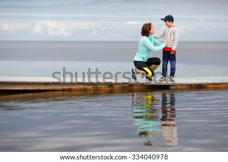 Young mother and little son walking together on wooden jetty - stock photo