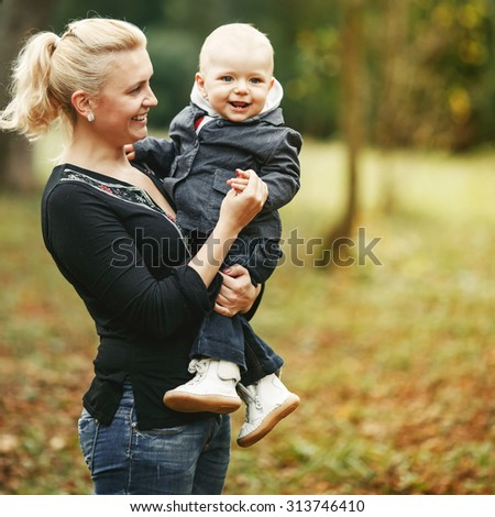 Young mother and lovely kid boy together in park.  - stock photo