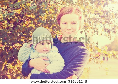 Young mother and newborn baby cute outdoor portrait in autumn garden. Vintage style toned image - stock photo