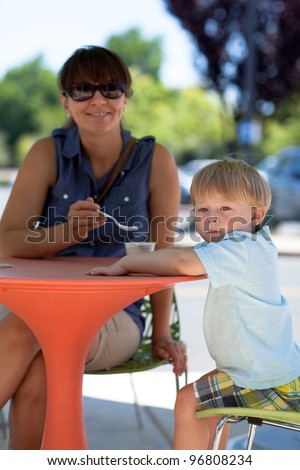 Young mother and son eating ice cream in a street cafe on a warm summer day