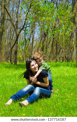 Young mother and son having fun in the woods