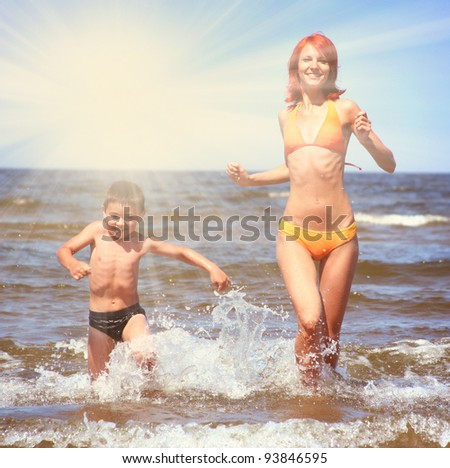 young mother and son having fun on the beach - stock photo