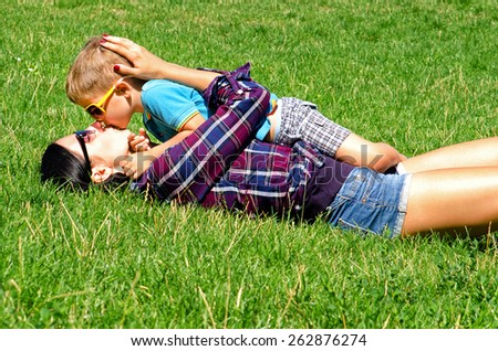 Young mother and son kissing lying on the lawn - stock photo