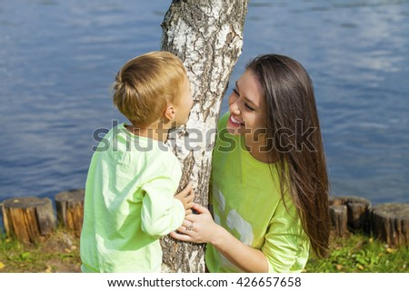 Young Mother and son playing in summer park. Concept of friendly family. - stock photo