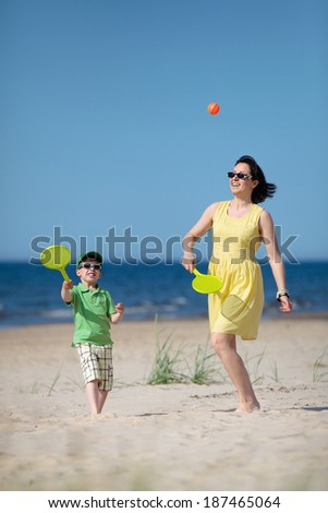 Young mother and son playing on tropical  beach - stock photo
