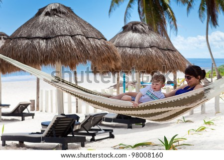 Young mother and son relaxing in a hammock on a caribbean beach - stock photo