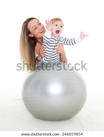 Young mother and sweet small baby with fitness ball on a white background. Healthy family. - stock photo