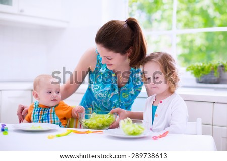 Young mother and two children cooking in a kitchen. Parent and kids cook dinner. Family with baby and toddler kid eat at home. Child preparing and eating vegetable lunch. Preschooler healthy nutrition