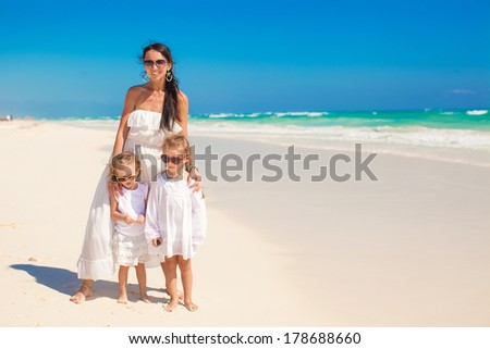 Young mother and two her cute kids at exotic beach on sunny day