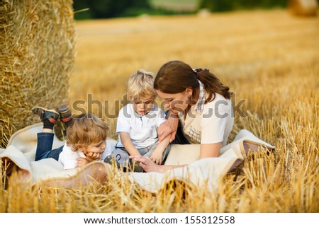 Young mother and two little toddler boys on yellow hay field in summer - stock photo