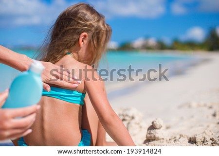 Young mother applying sunblock cream on little daughter's shoulders - stock photo