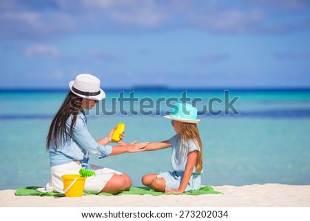 Young mother applying sunscreen on her kid - stock photo