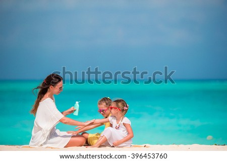 Young mother applying sunscreen on her kids - stock photo