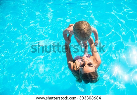 Young mother bathing in the pool with your child - stock photo