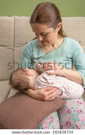 Young mother breast feeding her baby at home in a relaxed atmosphere - stock photo