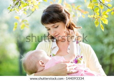young mother breast feeding her baby girl outdoors - stock photo