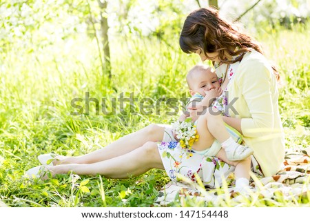 young mother breast feeding her baby outdoors summertime - stock photo
