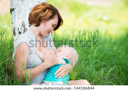 Young mother breastfeeding a baby in nature - stock photo