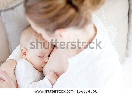 Young mother breastfeeding the newborm baby - indoors  - stock photo