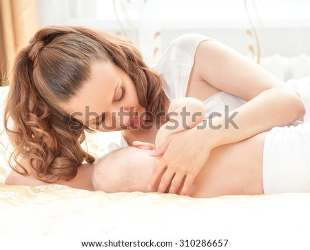Young mother breastfeeds her baby. Breast-feeding. Home interior.