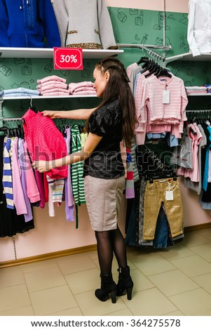 Young mother buys clothes for little child in children's clothing store