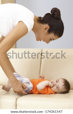 Young mother caressing baby boy on sofa, playing, smiling.