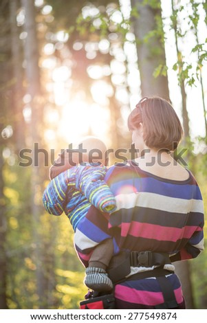 Young mother carrying her baby boy on a walk through a sunny forested area. - stock photo