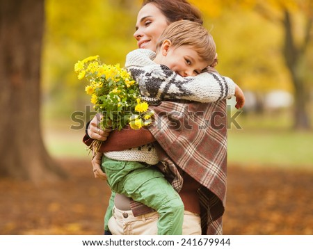 Young mother carrying her cute little son during walk in nature - stock photo