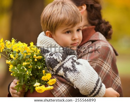 Young mother carrying her cute little son together with bouquet of flowers. - stock photo