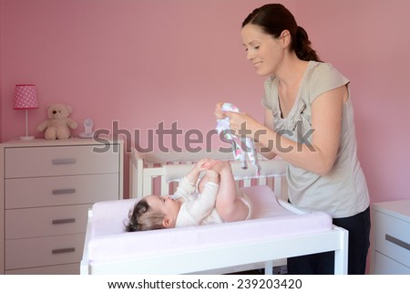 Young mother changes clothes on her baby (girl age 06 months). Concept photo parenthood and motherhood. - stock photo
