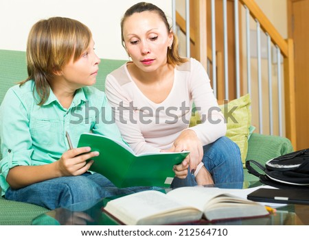 Young mother checking homework schoolboy son - stock photo