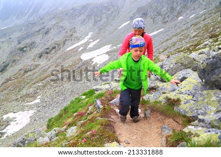 Young mother climbing along small boy on the mountain trail - stock photo