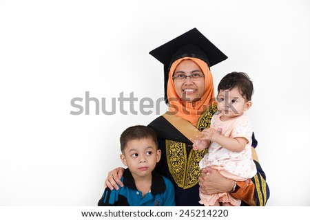 Young mother college graduate with her kids after convocation ceremony. - stock photo