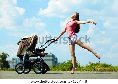 young mother dancing on a walk in the park with a baby in a stroller