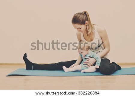 young mother does physical yoga exercises together with her baby - stock photo