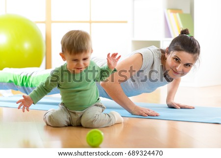 young mother doing yoga or fitness exercises with son kid
