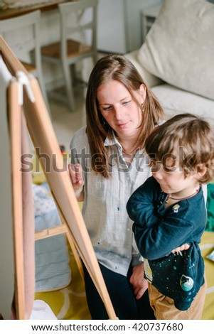 Young mother draws a chalk on a blackboard with his young son. The concept of family - stock photo