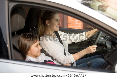 Young mother driving car to school with daughter