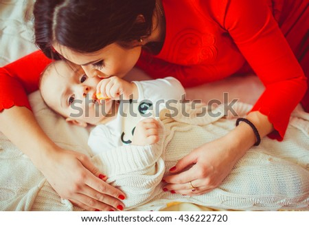 young  mother embraces her funny  child - stock photo