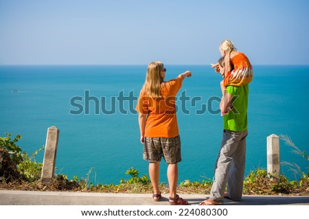 Young mother, father with daughter on fathers shoulders stay on mountain road along tropical island beach and look at ocean - stock photo